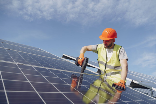 Man fixing a solar panel with a professional drill